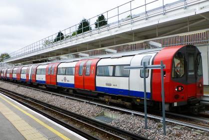 イギリス・ロンドン地下鉄チューブの国旗色の車両と曇天の空