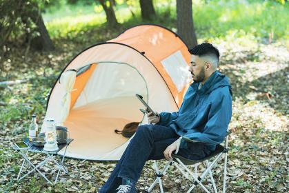 ソロキャンプイメージ・タブレット端末の画面を見る男性