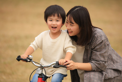 自転車に乗る練習をする親子