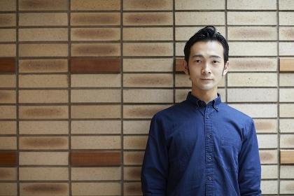 壁を背にした日本人男性のポートレート