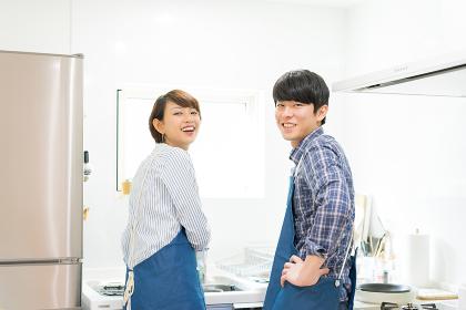 キッチンで振り返るカップル(エプロン着用)