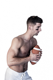 Shirtless rugby player holding the ball and focusing