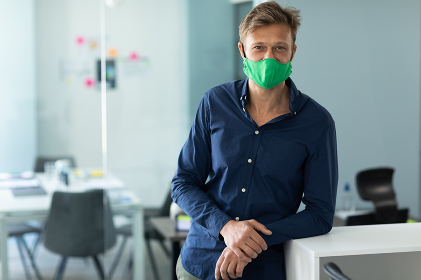 Caucasian man wearing face mask in an office. standing and looking at the camera. hygiene in workplace during coronavirus covid 19 pandemic.