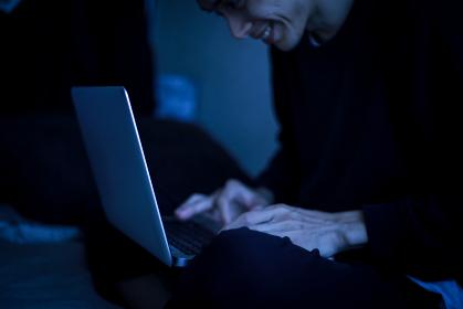 暗い中でパソコンを使う男性