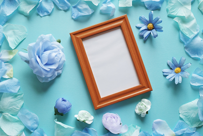 青を基調とした造花と背景。中央に縦長斜めの木製フォトフレームの白いコピースペース。平置きの俯瞰撮影。