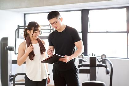 カウンセリングをするアジア人男性パーソナルトレーナー