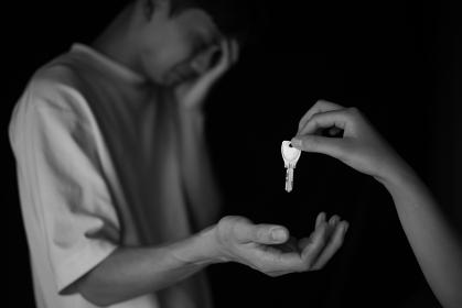 泣きながら鍵を受け取る男性