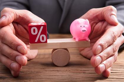 Human Hand Protecting Balance Between Percentage And Piggybank