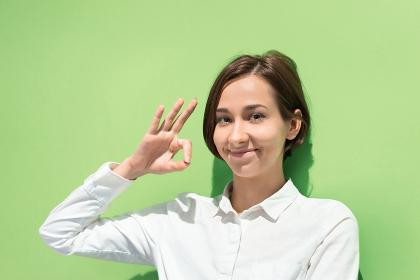 OKマークをする若い女性(カラフルな色の背景)