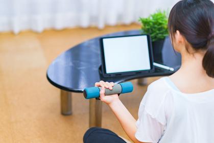 リビングで配信動画を見つつ冷え症対策にダンベル運動をする若い女性【ニューノーマルのライフスタイル】