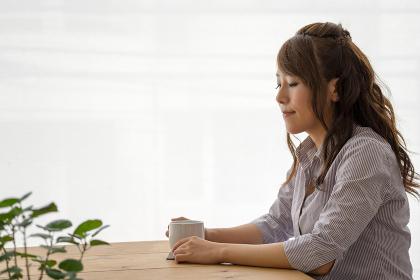 カフェでホットドリンクを飲む女性