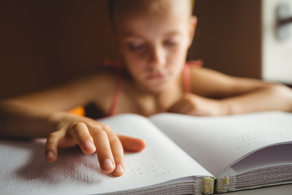 Little girl using his right hand to read braille
