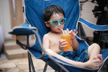 水着で飲み物を飲む男の子