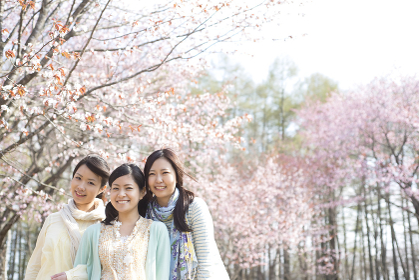 桜の前で微笑む3人の女性