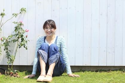 バラの咲く庭に座る女性