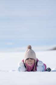 雪原で雪だるまと微笑む女の子