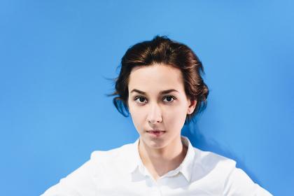 オールバックの髪型をした女性(青色の背景)