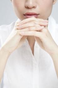 顔の前で手を組む女性