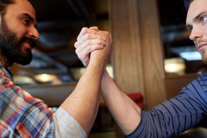 close up of men arm wrestling at bar or pub
