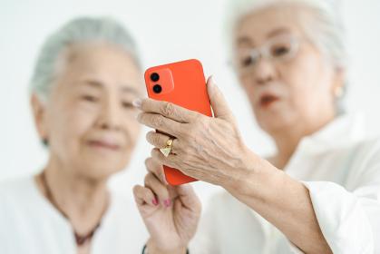 試行錯誤しながらスマートフォンを操作するシニア女性たち