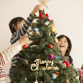 クリスマスツリーの飾り付けをする子供達