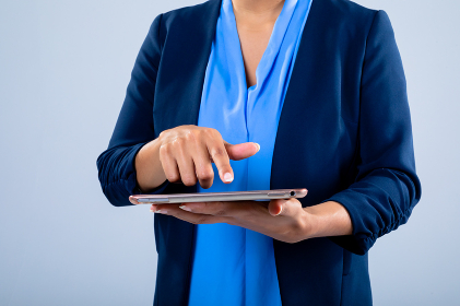Mid section of businesswoman using a digital tablet against grey background. business, professionalism and technology concept