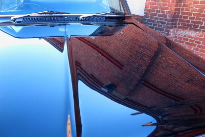 古い乗用車のボンネットに写り込んでいる、レンガ倉庫の壁