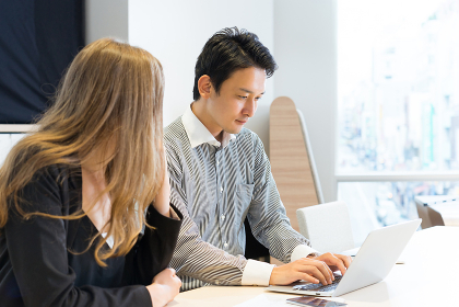 ノートパソコンで仕事をする男性と女性(人種の違う人々)