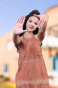青空とオレンジ色の建物の前で涼しげなくすんだオレンジ色のワンピースを着て前髪をあげた黒髪ロングヘアの笑顔の女の子が両手を前に突き出し指で四角の枠を作っているポーズ