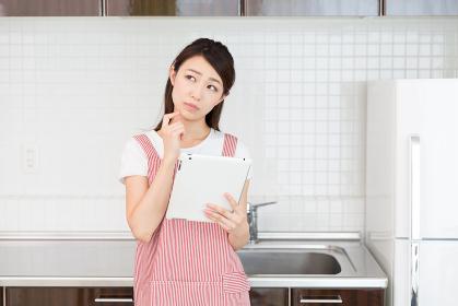 タブレットを見ながら料理をする女性 考える