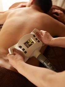 機械で腰のマッサージを受けるアジア人男性