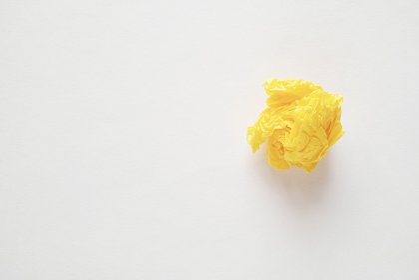 灰色の紙の右側に置いた黄色の紙礫とコピースペース