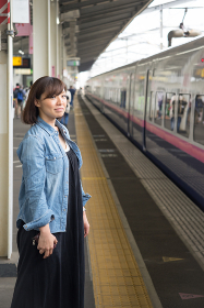 駅のホームに立つ女性(旅行・汎用・新幹線・交通)