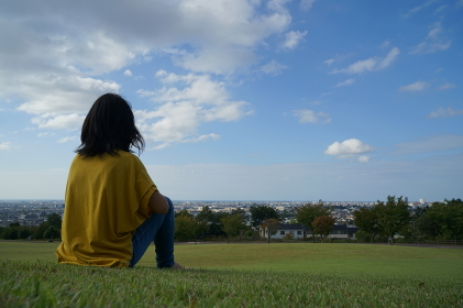 眺めの良い公園で青空のもと芝生の上で左側にいる座った後ろ姿の1人の女性
