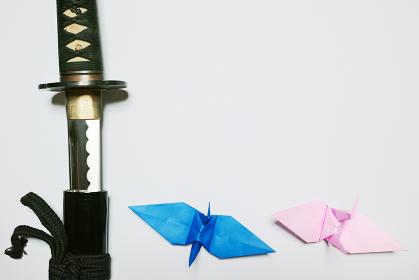 白い紙の左端に配置した抜きかけの日本刀と下に配置した青とピンクの折り鶴
