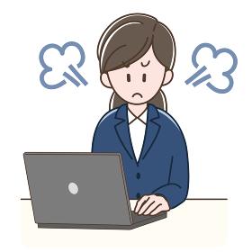 パソコンの前で怒るスーツの女性