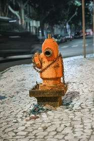 Fire hydrant centered in a selective focused night shot of a street, b