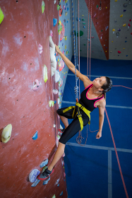 Woman practicing rock climbing in fitness studio