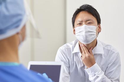 喉の痛みを伝えるマスクをつけた日本人男性