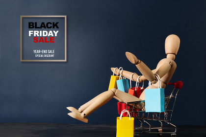 Black Friday sale, wooden doll sitting on shopping cart with sho