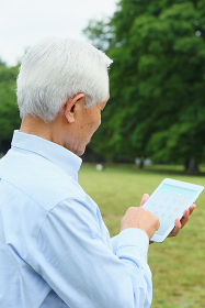 iPadを操作するシニアの日本人男性