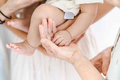 赤ちゃんを抱っこしてふれあうシニア女性