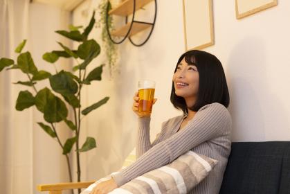 夜の部屋でビールを飲む若い女性