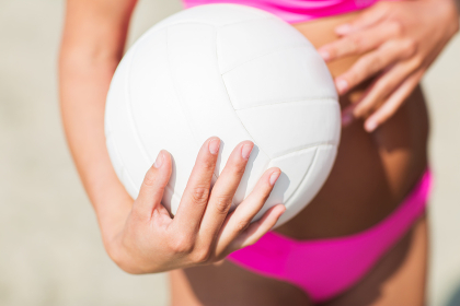 close up of woman with volleyball ball on beach