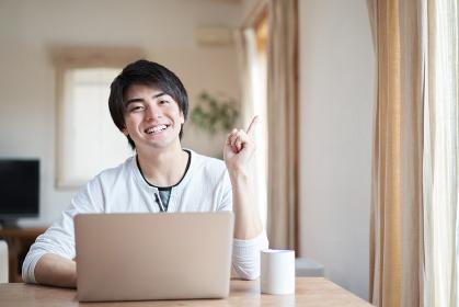 パソコンを操作しながら指差しをするアジア人男性