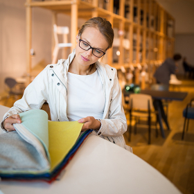 Pretty young woman  choosing the right material/color for her modern appartement interior (shallow DOF  color toned image)