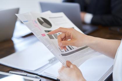 会議資料を見る日本人女性ビジネスウーマンの手元