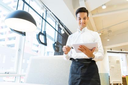 タブレット端末でクレジットカード決済をする男性の店員