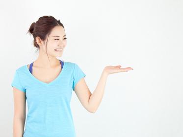 スポーツウェアで案内をするアジア人女性