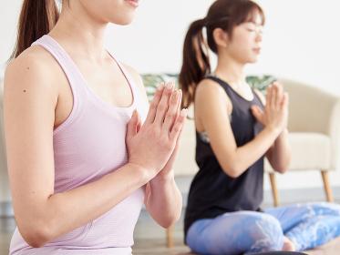 ヨガで瞑想をするアジア人女性